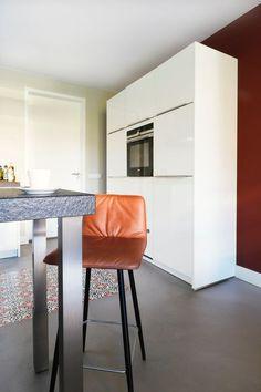 Een warm rode kleur in de keuken maken de keuken wat minder steriel. Het past nu beter bij de woonkamer. Hier hebben we ook gekozen voor een prachtige tegelvloer in een strakke vloer.  De kruk is van KFF, soepel leer.  Wil je ook interieuradvies om een buiten je comfortzone te denken?  STYLING22 helpt je, je hoeft alleen maar te bellen;-)<br>