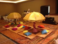Mehndhi set up and decor, umbrellas, mats and cushions.