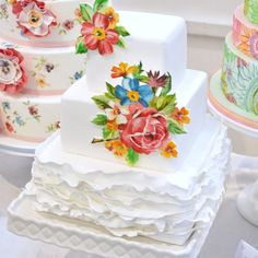 Bold hand-painted blooms add a joyful look to any ivory cake! Amazing floral wedding cake.