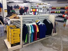 Work wear displays.  Slatwall boards fitted around the wall in a grey finish with a variety of slatwall chrome accessories, slatwall arms, D rails, slatwall hooks etc   Gondola shelving in the centre of the store with end units to either side.