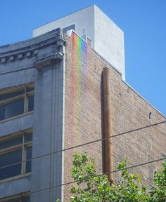 An anonymous street artist in Albuquerque, New Mexico spills paint over the edge of neglected buildings mixing graffiti and art into a beautiful illegal rainbow.