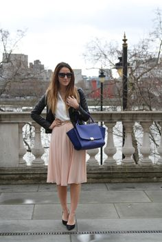 White button down shirt outfit idea with leather jacket, peach pleated skirt, black flats and blue handbag