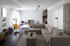 O living é dividido em dois ambientes: em primeiro plano, a sala de TV, com sofá em L