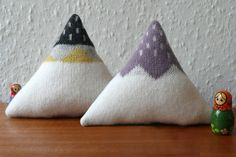 Each mountain is made from 100% lambswool, which has been knitted and felted to create a super soft fabric. The triangular shape is perfect for cuddling and looks great propped up on your sofa to make your own Rocky Mountain scene.  http://hilarygrant.bigcartel.com/