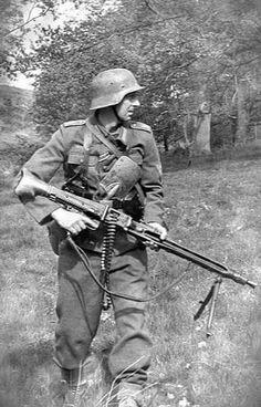 Soldado alemão empunhando uma MG-42 com a tipica cinta de 50 tiros. Data e local desconhecidos. Se alguém souber, favor informar nos comentários. A pá na cintura, além da função de cavar, podia ser usada como arma em combate corpo-a-corpo. Muitos alemães a preferiam no lugar da baioneta.