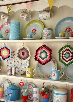 Hutch crowned with bunting, full of bright floral and dotted dishes with potholders on cup hooks @ Coco Rose Diaries