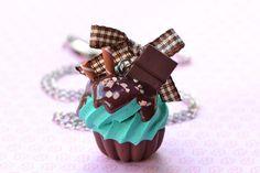Cupcake de menta com calda de chocolate. Produto feito a mão. Podem haver pequenas diferenças de uma peça para outra. Leia atentamente as políticas de compra da loja. Confira as medidas.  Para calcular o frete basta adicionar o produto em sua cesta de compras.  CLIQUE NA FOTO PARA AMPLIAR.  Materiais: cerâmica plástica, metal prateado Medidas: cupcake: 2,5 cm de altura corrente: 50 cm R$32,00