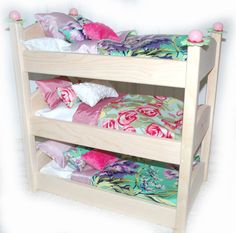 "A superior quality 18"" triple doll bunk bed handcrafted out of the finest knotty pine. The entire bed is extremely sturdy, seamless, and sanded to a soft finish. Beautiful designer linens included! •"