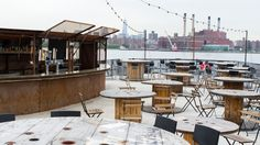 The Brooklyn Barge is a floating restaurant located on the NYC waterfront. The nearby chairs are movable around the fixed tables, creating an array of seating options for visitors.