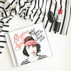 Blusa listra branca com listras pretas, batom vermelho ruby woo da M.A.C e o cd What we sar from the cheap seats da Regina Spektor