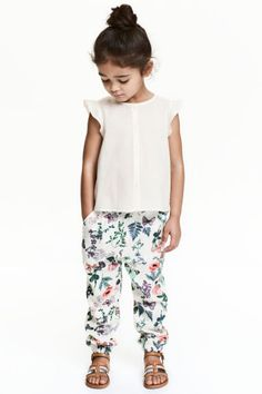 Patterned pull-on trousers: Pull-on trousers in a patterned viscose weave with elastication and a decorative bow at the waist, side pockets and elasticated hems.