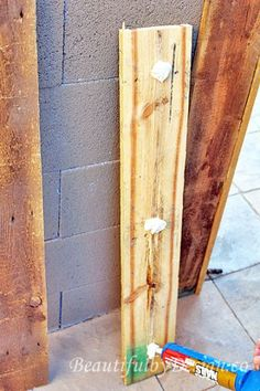 Using liquid nails to attache the pallet wood panels to the underlying cinder block base, from BeautifulbyDesign.co