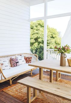 A Brisbane fixer-upper was revived by A Pair and A Spare This deck features a timber dining table with matching benches that complement a wicker day bed. A colourful rug adds a pop of fun to the space. Outdoor Curtains, Outdoor Rooms, Outdoor Dining, Outdoor Decor, Outdoor Dinning Table, Fixer Upper, Table Farmhouse, Brisbane, Timber Dining Table