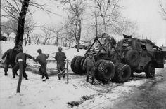The crew of an M26 tank retriever Dragon Wagon called 'Little Chicken' prepare to right an M36 tank destroyer overturned on an icy road near Fisenne, january 1945. Little Chicken is from 2nd Ordnance Maintenance Battalion.