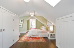 attic bedroom with ancient marble accent wall, white bedroom with sloped ceilings, celery green accent wall, lime green used in interior design, yellowish-green, wood floors, orangish-red area rug, pink bedding (sherwin williams, ancient marble)