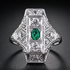 A modestly proportioned, yet bright and vibrant old mine Colombian emerald is the focal point of this sophisticated and artfully sculpted platinum and diamond dinner ring hailing from the peak of the Art Deco period- circa 1925. Multi-dimensional geometric planes, accented with decorative openwork, fine milgraining and hand engraved  details sparkle with old European-cut diamonds. This crisp and stunning Art Deco jewel measures just over 3/4 inches long.