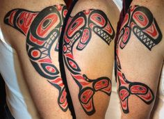 Haida Orca (Killer Whale) tattoo on the upper arm in black and red.