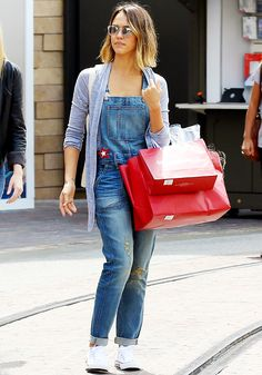 Jessica Alba in denim overalls, white sneakers, and sunglasses