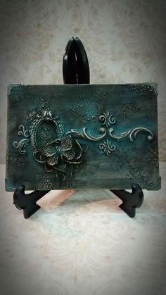 Mixed media on mini canvas. Decorations made of clay. Black acrylic paint and patinas for aging the piece. Make nice things with just a few supplies!