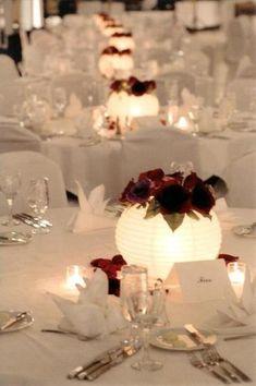 Paper lanterns with flowers as centerpieces. A couple votives and flower petals surround. Paper lanterns with flowers as centerpieces. A couple votives and flower petals surround. Paper Lantern Centerpieces, Inexpensive Centerpieces, Banquet Centerpieces, Non Flower Centerpieces, Unique Wedding Centerpieces, Wedding Paper Lanterns, Centerpieces With Lights, Chinese Lanterns Wedding, Diy Paper Lanterns