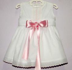 Vestido para bebe niña en batista blanco combinado con tirabordada rosa. Adornado con fajín y lazo rosa a juego. Forrado en batista. - Primavera/Verano - MiBebesito. Ropa de Bebe hecha a mano