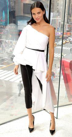 Adriana Lima in a one-shoulder white top, leggings and heels
