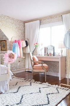 Feminine bedroom with a large area rug, gold wall paper, and a white rolling rack