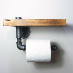 Add a little Industrial/Urban chic to your bathroom Combining a handy wooden shelf and using iron pipes to make the sturdy roll holder.