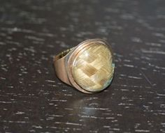 """1798 Mourning Ring, Rose gold ring with a circular compartment containing two shades of hair in a basket weave pattern under glass.   Inscriptions: Back: """"Josiah Quincy jun e / Obt, , 26 april 1775 aet. 31, / and Abigail Quincy / Obt,, 25 March 1798, aet, 53""""\n \n Band: """"JQ to HS"""" (Engraved)"""