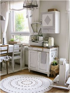 Vintage cabinet with sweet, little feet, prettily-dressed chairs, and gray paints.