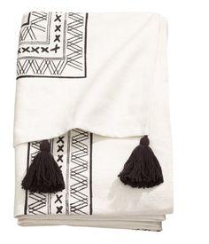 Tagesdecke aus Baumwolle mit Musterdruck auf der Oberseite und weichen Acrylquasten an zwei Seiten.