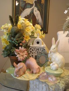 Easter Table Scape 2012  Asian silk scarf, moss topiary rabbit, daffodils in white swirl glass vase, white wood birdhouse, verdigris metal frame, terra cotta rabbits, small ceramic box with petit bunny, jewel eggs and a Teena Flanner paper mache Rabbit.