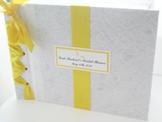 A custom bridal, wedding guestbook covered in white cotton lace fabric with color satin ribbon and cardstock accented to matchyour color scheme, is a fun and different style for the bride-to-be before her big day to display well wishes from family and friends and insert photos from the event.
