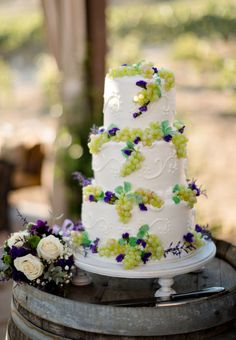 The three-tiered white wedding cake was decorated on the top and sides with green grapes and small purple flowers and swirls in white. The cake was positioned on a simple white cake stand. Fine Art Wedding Photography Courtney McManaway Photography Lake Elsinore, CA More Great Looks Like This
