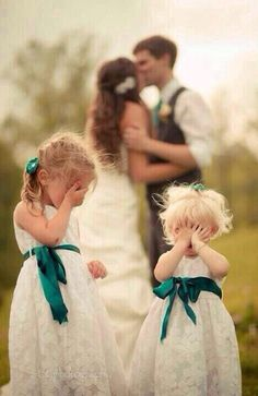 Flower girls shy of the bride and groom kissing