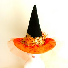 A big beautiful glimmering harvest moon is represented in the brim of our Harvest Moon witch hat.  Shimmery orange velvet is overlaid with sparkling veil of orange tulle. An autumn mum and glittering