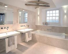 photo of beige cream white limestone tiles bathroom with bath his and hers sinks mirror mirrors tiles