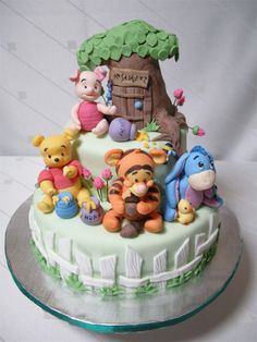 Baby Pooh  Friends Cake - A cake featuring gumpaste figures of Pooh and his friends Tiger, Eyore and Piglet, in their baby versions. The tree house was made of sculpted rice crispies and covered with fondant like the cake, in other the cake be all edible.