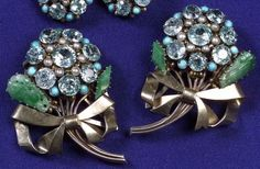 Dorrie Nossiter. Arts and Crafts gem-set and hardstone pair of clip brooches set with blue zircons, turquoise, seed pearls and jadeite, mounted in gold and silver. Part of a dress clip and earclip set, unsigned. original fitted and signed presentation box. Sold by Skinners, Boston, USA. View 3: the dress clips.