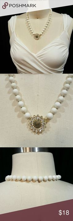 White bead sunflower necklace Really pretty white plastic bead necklace with crystal-like sunflower and front closure from Macy's. Jewelry Necklaces