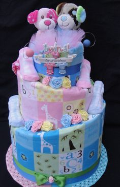 Twin boy/girl Diaper cake made with 80 Pampers diapers, 2 blankets, 2 matching bibs, 4 pairs of socks, 1 ornament, 2 animal embroidered snuggly blankets and garnished with ribbon and tulle.  Another http://www.facebook.com/DiaperCakesbyDiana creation.