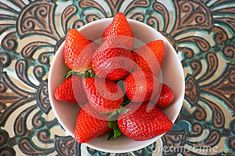 Big strawberries in a white deep plate on a pattern table in Spain