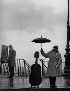 Robert Doisneau: Musician in the Rain, Maurice Baquet, Paris, 1957.