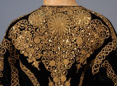SILK VELVET JACKET with GOLD CORD and SEQUINS, c. 1870. Midnight blue bolero style with peplum, heavily decorated in metallic gold cord and sequins in an ethnic style pattern, lace trimmed sleeve, silk lining. Purported to have been purchased from House of Worth as fancy dress.