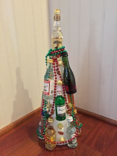 Mini booze tree for Yankee gift swap/white elephant made from foam cone, mini alcohol bottles, Mardi Gras beads, and pom poms.  Cost about $25.