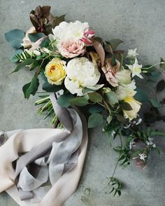 Vintage Florals created the bride's romantic bouquet using peonies, roses, jasmine, and greenery. Gray silk ribbons held the arrangement together.
