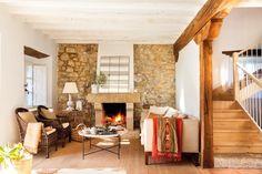 sala de estar con chimenea y pared de piedra en una casa rustica