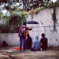 Namaz kılan genclere şemsiye tutan genç