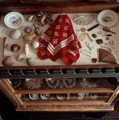 A shelf on top of the doll's house in the treasure room at Hill Top, filled with shells, miniature fans and other doll's accessories, around Peter Rabbit's red and white spotted kerchief.