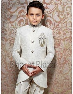 Your little sweetheart will look fabulous by wearing this dashing white color self paisley design jacquard fabric indo western sherwani. Designed with shiny kundan, pearls work high neck collar, decorative buttons and brooch. Comes with matching breeches.